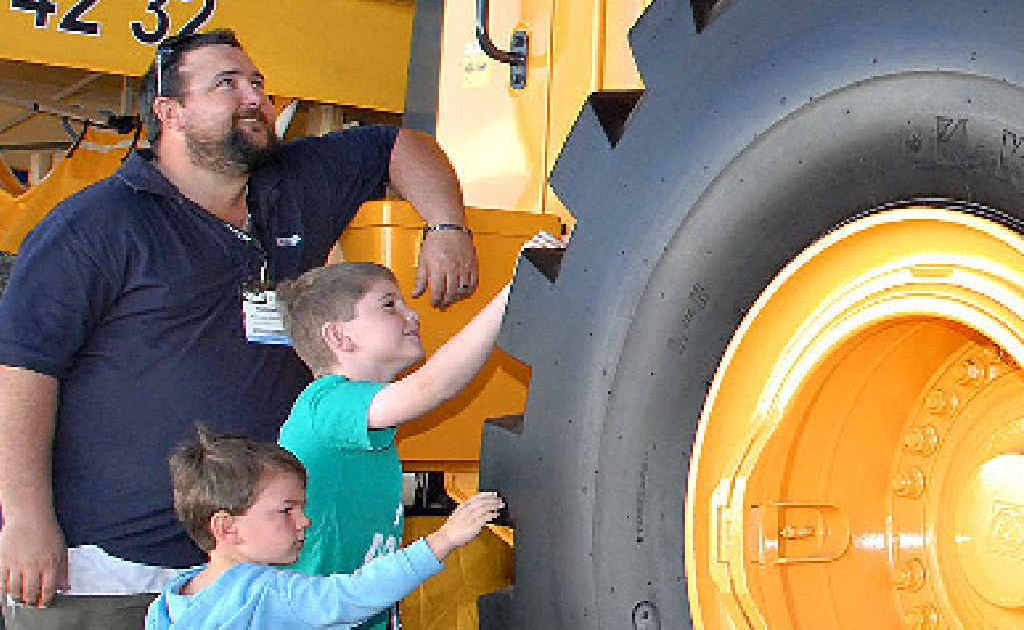 Michael Stanton, of Eimeo, and sons, Jack and Charlie, check out the heavy equipment on display at QME.