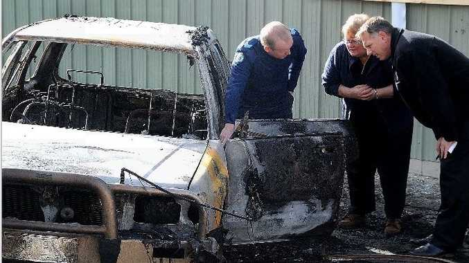 Gympie police forensics officer John Kane and detective David Britton investigate a burnt-out car with the vehicle's owner at Barter St Complex.