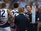 Adelaide Crows coach and his players talk tactics during an AFL game.