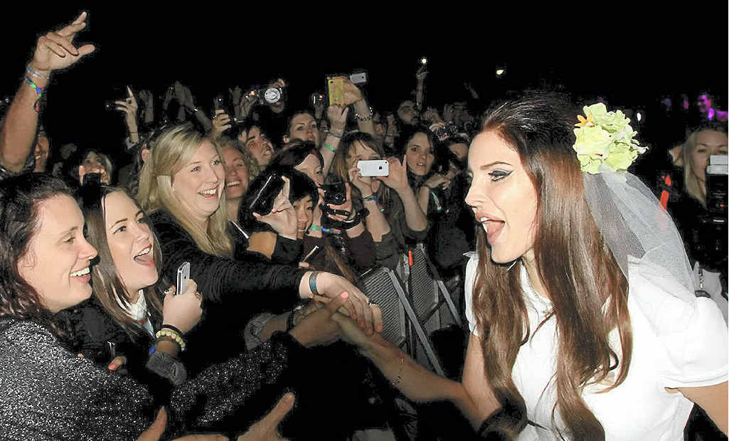 Lana Del Rey wearing a wedding dress gets close and personal with fans.