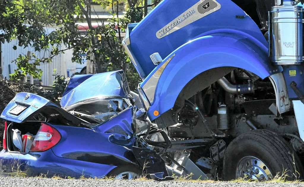 A woman died when a sedan and a B-double truck collided on the Bruce Hwy yesterday.