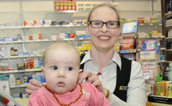 Five-month-old Sarah Hunt tries on an amber teething necklace as Judy Wielandt from Southtown Pharmacy looks on.