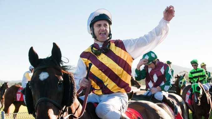 Jockey Danny Nikolic salutes the crowd as he returns to the winners circle after winning the 2012 Calton Mid Coffs Harbour Gold Cup on Pepperwood.