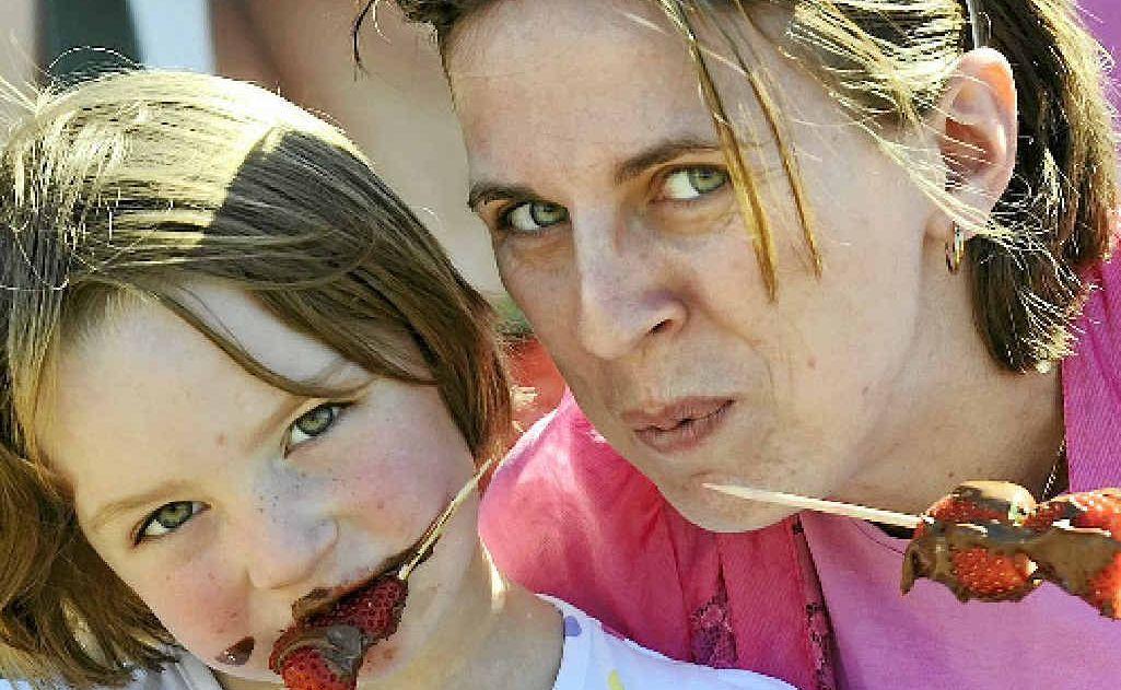 Ella Bainton and Jessica Bevan enjoy chocolate-coated strawberries at Saturday's Strawberry Fair.