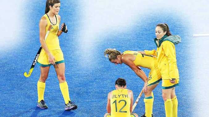 Hockeyroos stalwart Hope Munro (right) consoles her team mates after missing out on the women's hockey semi-finals in London.