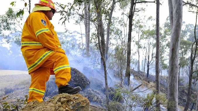 A Rural Fire Service volunteer watches over burning bushland just off the Old Glen Innes Rd.