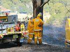 Rural fire crews extinguish a grass fire that threatened several homes at Obi Obi.