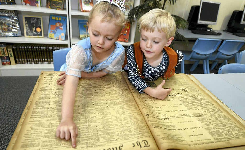 Jasmin Maycock and Alex Winter, both 5 and in prep at Depot Hill State School, find lots of interest in old editions of The Morning Bulletin that were found in the school's storage area.