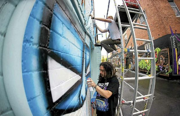 WALL ART: Back Alley Gallery project manager Nathan Eyres (bottom) brightening up Lismore's lanes.