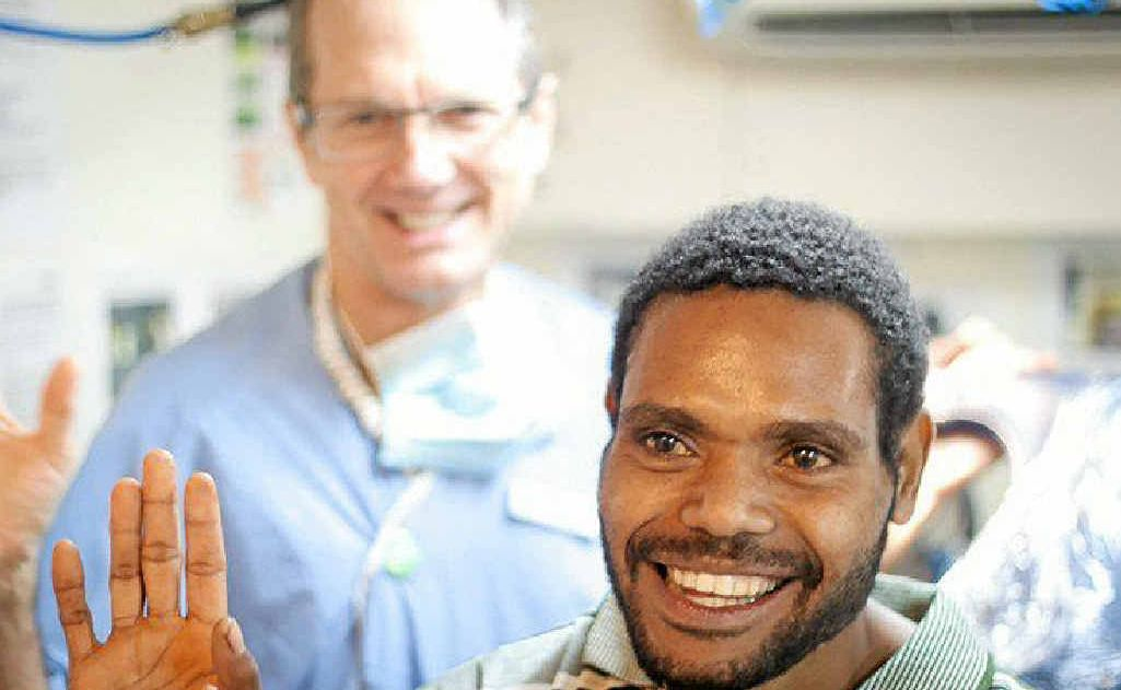 SMILES ALL ROUND: Alstonville dentist John Philips with a PNG patient.