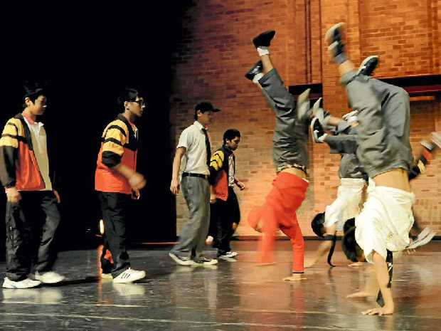 Cast members of The Yard pull a group handstand in rehearsal.