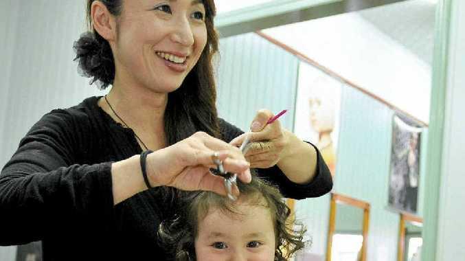 Hair stylist Marina McCaul gives her daughter, Mieko, a trim. Mrs McCaul says Asian hair requires different cutting techniques.