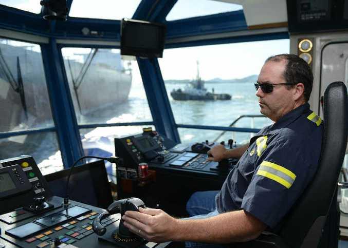 Onboard the SMIT Yallarm, tug master John Sharp guides a coal ship into dock.