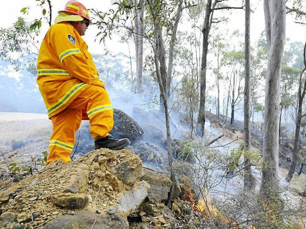 A Rural Fire Service volunteer watches over burning bushland. A number of escaped fires have rural firefighters hot under the collar.