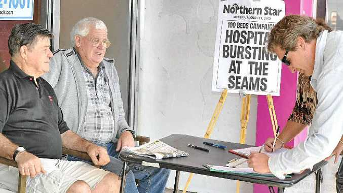 Marshall Fittler (left) and John Bigelow welcome Scott Marshall's signature on their petition for more beds at the Lismore Base Hospital.