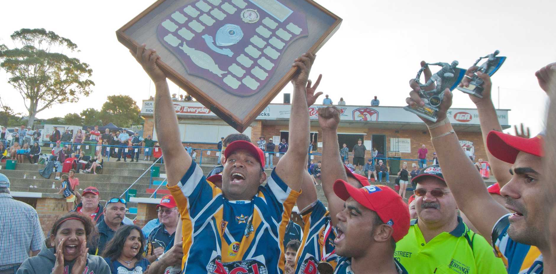 Fifty years of disappointments are wiped away as Macleay Valley captain-coach Willie Lockwoodd hoists that elusive premiership shield.
