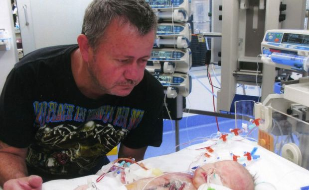 Darryl Marshall watches as his son Matthew is baptised at the Brisbane Mater Hospital.