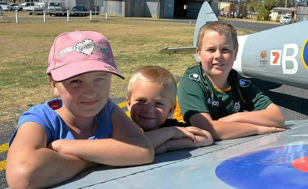 Kayla Carney, Josh Matthews and Josh Niebling admire some of the aircraft at Wings Over Warwick at the weekend.