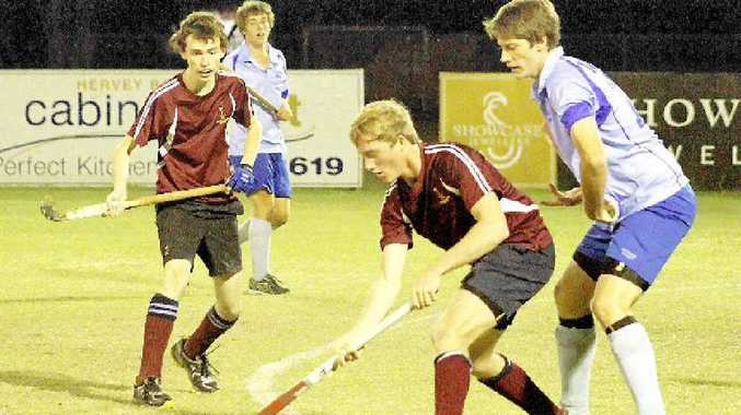 Flames player Jack Brookes shields the ball from Brothers' Ben Brown in the Hervey Bay Hockey Association men's division one grand final.
