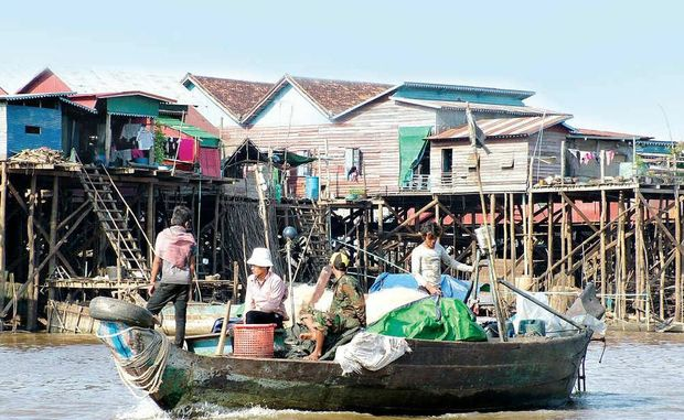 A fishing boat passes in front of stilted houses in Cambodia's Tonle Sap lakeside community of Kompong Khleang.