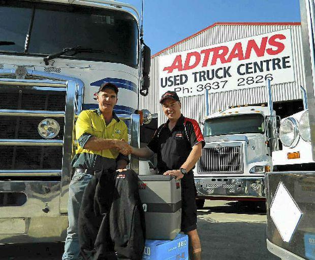 WINNER: Steven Birt wins a Waeco fridge from Adtrans Eagle Farm manager John Defries.