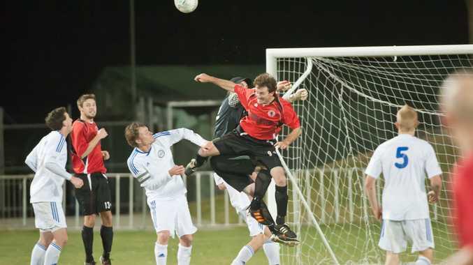 Coffs United striker Ben Mackay challenges with Storm keeper Mitch Weeden for the ball.