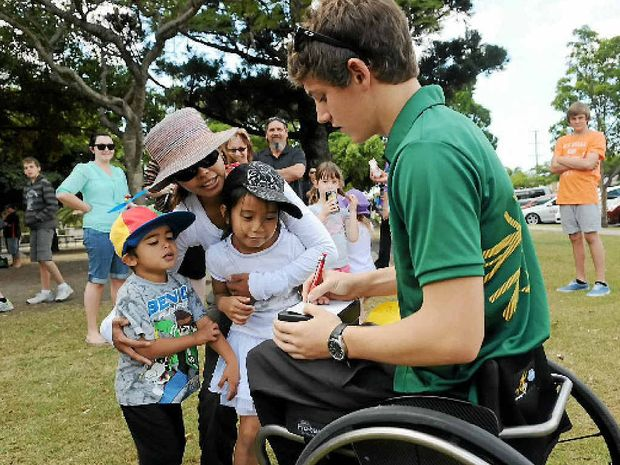 Paralympian Rheed McCracken signs autographs for Jai, Lorena and Erika Edey at the welcome home event held.