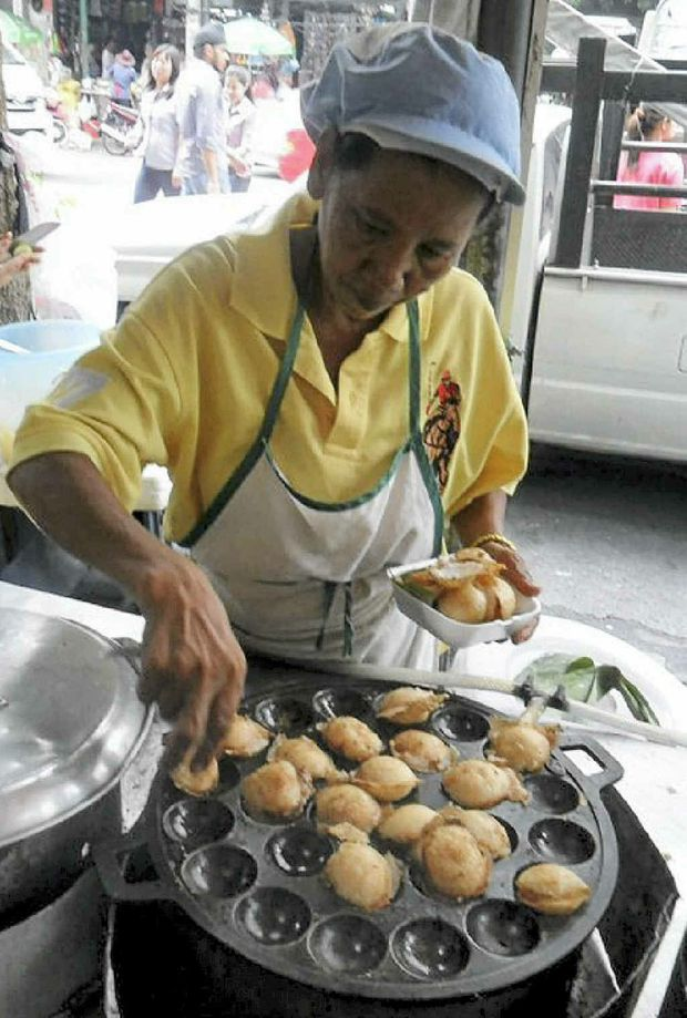 A woman makes a mountainous heap of crispy chicken on the streets of Bangkok.