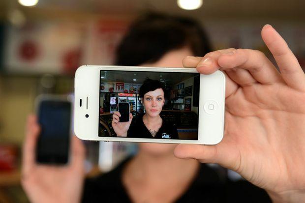 Kirsty Watt. Scam messages on phone. Photo: John Gass / Daily News