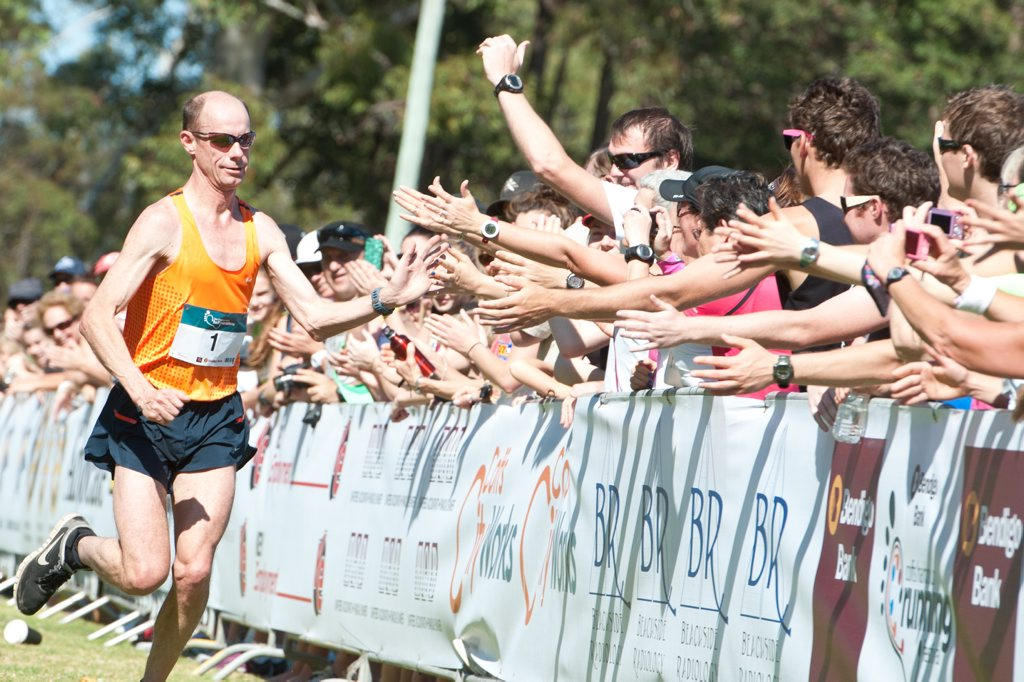 Steve Moneghetti celebrates with the crowd as he secures his second Coffs Harbour Half Marathon title.