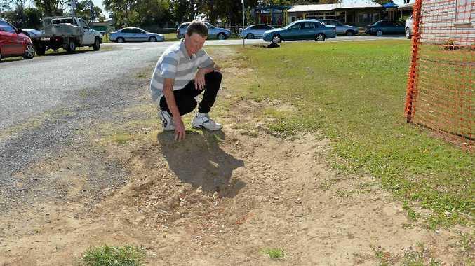 Ian Barbury checks the damaged laneway alongside his West Mackay property.