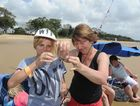 Holiday makers from Brisbane , Mandy Taylor helps her daughter Charlotte bait the rod in the hope of catching a feed. They are pictured at Torquay, enjoying the Fraser Coast.