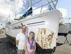 Mark and Pat Meulman of Mackay beside their damaged catamaran which is dry-docked in Yamba after colliding with a whale off the coast of Yamba.