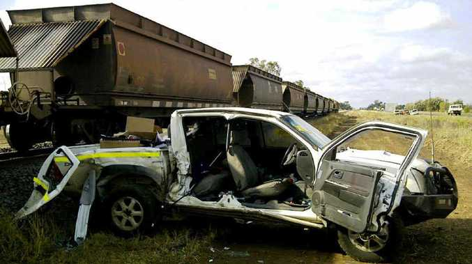A truck lies in ruins after it collided with this 98-carriage coal train early yesterday at an Emerald level crossing.