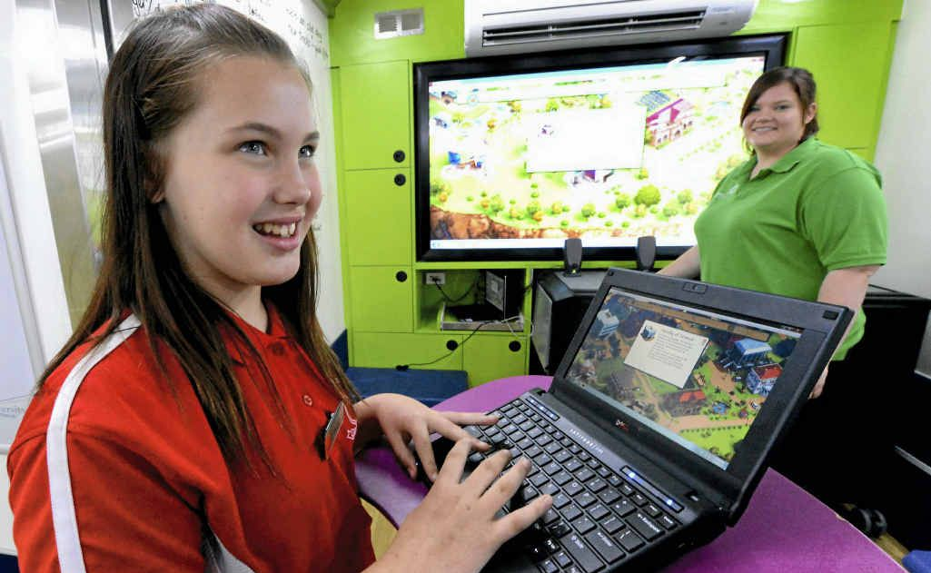 Lakes Creek Primary School captain Abbey Gull, assisted by participation officer Sarah Law, tests the interactive tools.