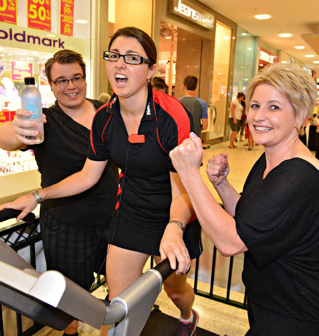 Weary NewsMail editor Christina Ongley gets encouragement from Hitz FM's Damo and Trace as she pounds the treadmill in the I Can for Cancer treadmill challenge.