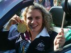 Jacqueline Freney shows off one of her medals as she drives in a parade through Lennox Head on October 2, 2012.