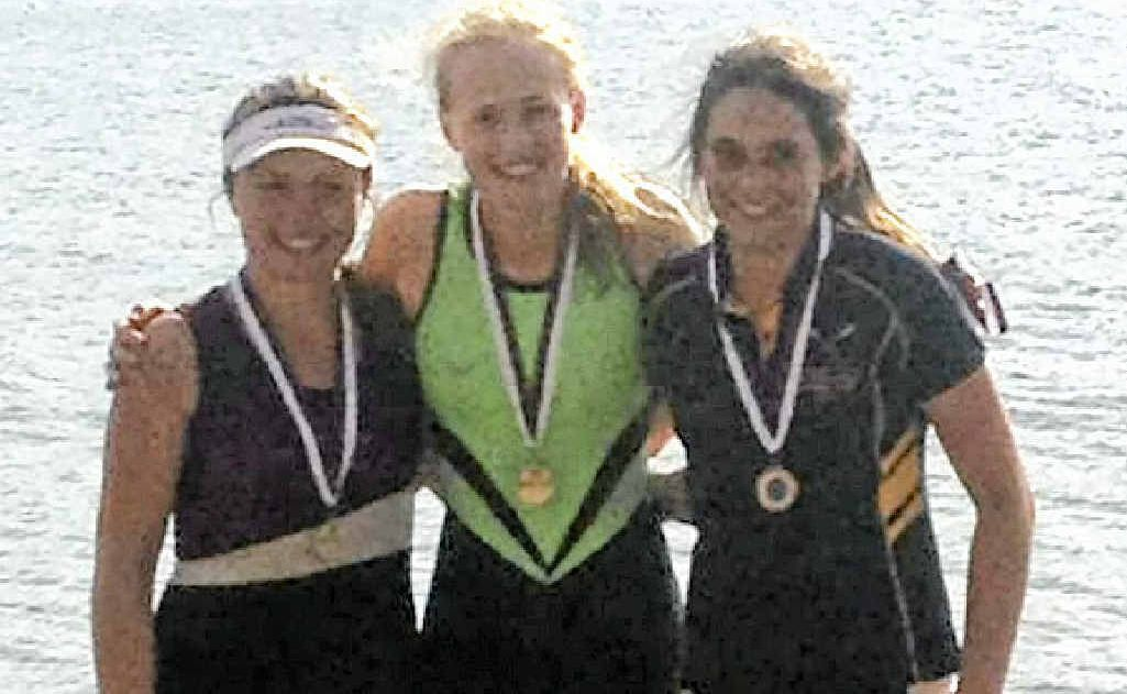 Harriet Hudson (centre) after a state title victory in rowing at Bundaberg.