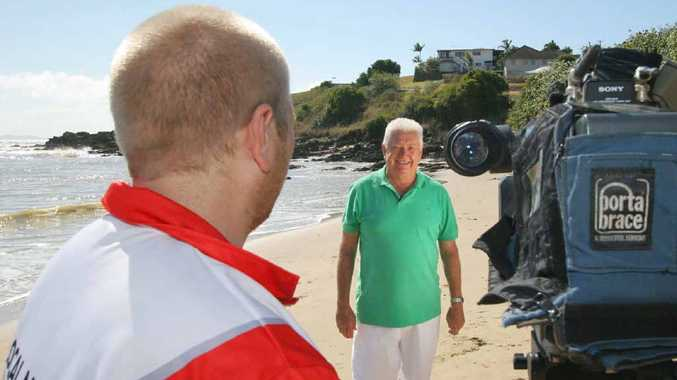 Weatherman Peter Byrne, in front of a 7 Local News camera at Cooee Bay, signals a return to television.