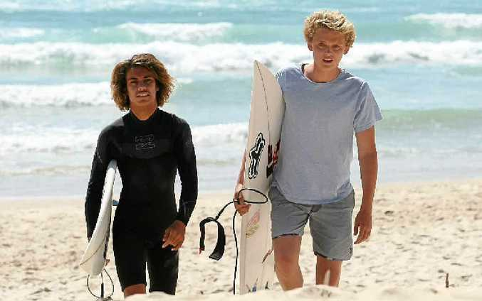 WAVE OF SUPPORT: Dylan Crawford (left) and mate Josh Atkins at Duranbah Beach. Photo Blainey Woodham / Daily News