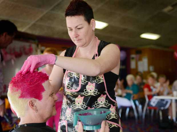 Hairdresser Annette Parker changes the colour of Sue Wright's hair at the Pink Ribbon Fundraiser breakfast at the Gladstone Golf Club yesterday.