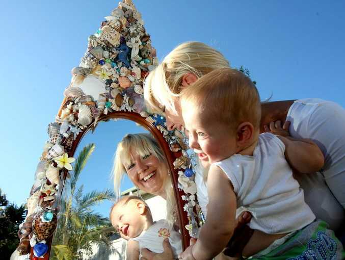 Artist Belinda Endler and son Frankie Capps with her surfboard mirror.