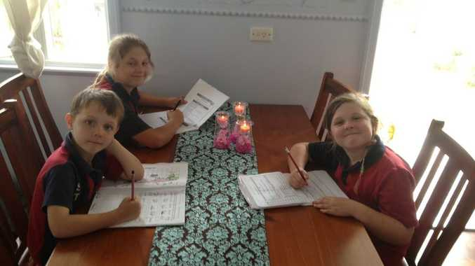 Caleb, Annika and Holly do their homework with their mum Elizabeth Davies nearby to watch over them.