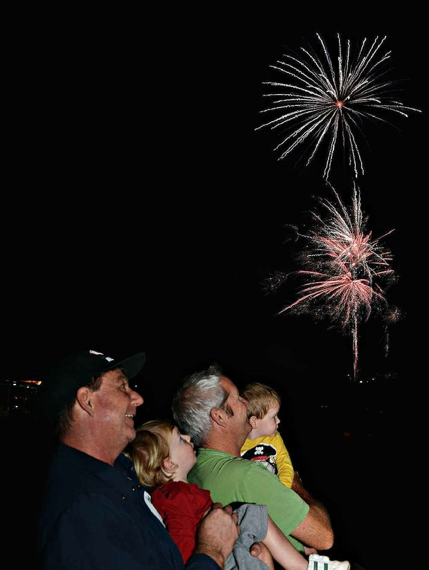 Paul Cummin with Lachlan (left) and Jock Hansen with Noah enjoy the fireworks that ended the River2Reef Festival.