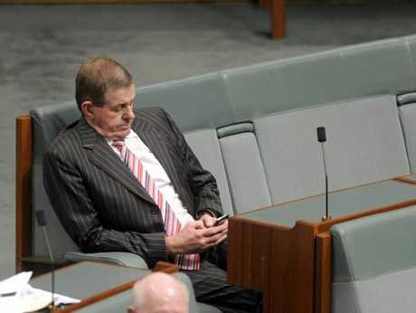 Peter Slipper sends text messages from his phone during Parliament.