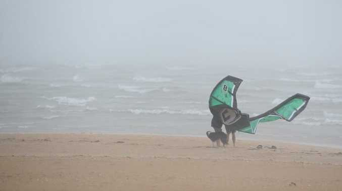 This kiteboarder gets his kite back on the beach at Pialba as the rain starts bucketing down. Photo: Alistair Brightman / Fraser Coast Chronicle
