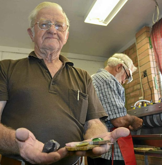 Warwick Lapidary Club president Syd Woodrow holds stones at various stages of processing. In the background, John Smith shapes his stone.