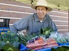 Gardening Australia host Jerry Coleby-Williams inspects the produce from the Mr Organic stall.