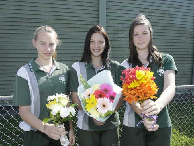 Ashleigh Tyler, Brittney Reibelt and Adair Scully-Schild bring flowers to school to lay in the paddock for the Caboolture High School alpacas that were beaten to the point of death on Saturday morning.
