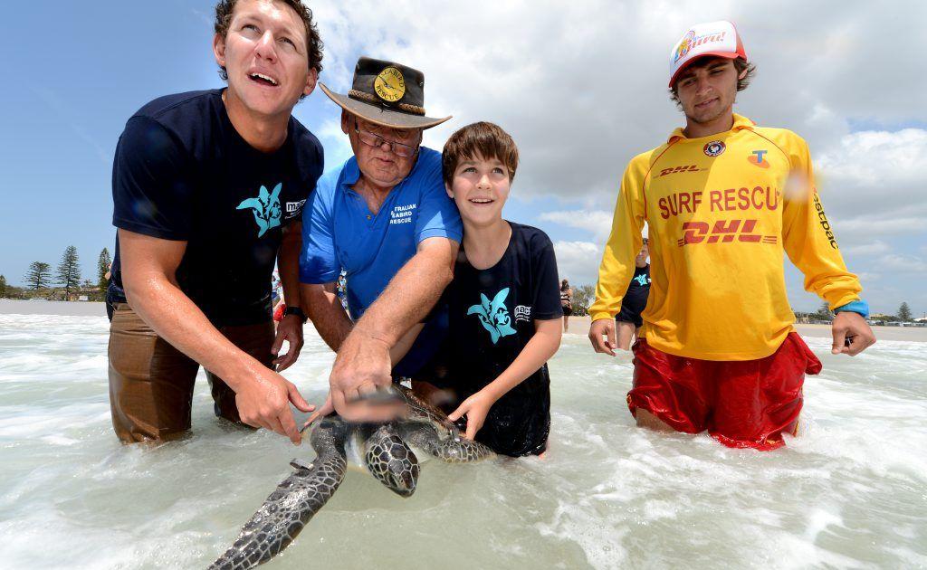 Tim Adams, Ron Potter, Josh Petty and Fletcher Rainford-Markarian release Macs the turtle at Kingscliff Beach.